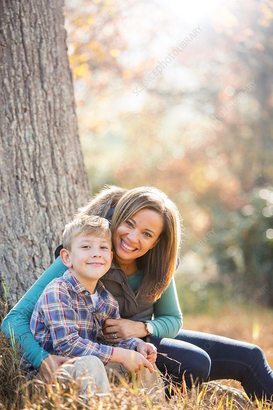 Mother and son at tree trunk