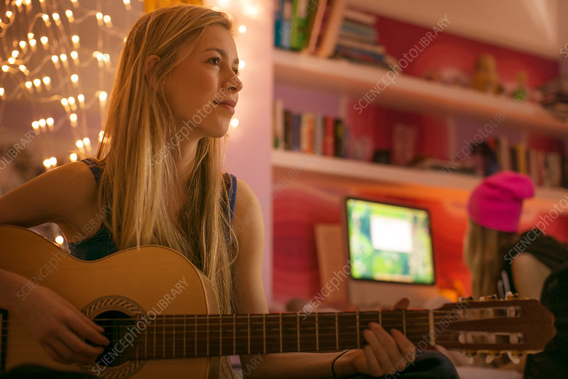 Teenage girl playing guitar in bedroom
