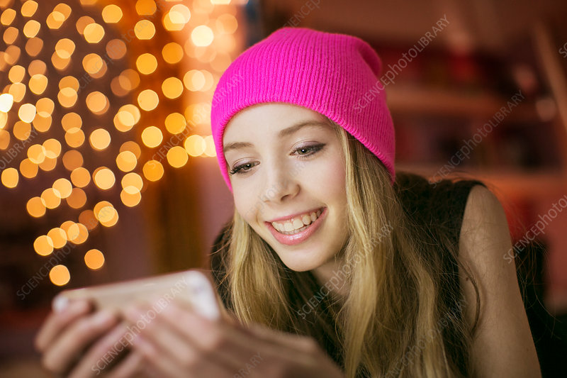 Teenage girl in pink beanie texting
