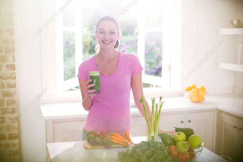 Woman drinking green smoothie in kitchen
