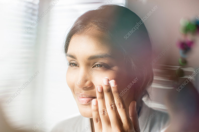 Close up woman applying moisturizer