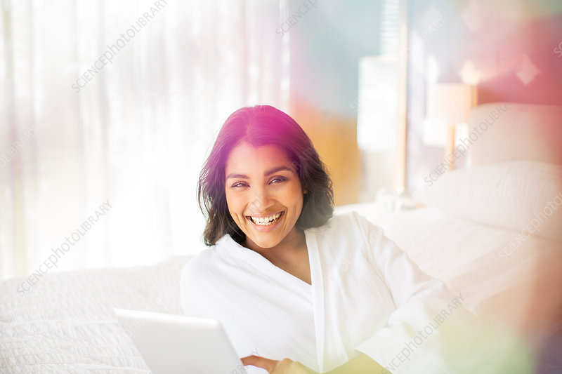 Woman in bathrobe using tablet on bed