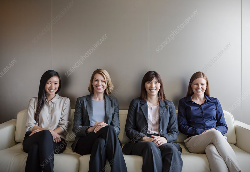 Businesswomen sitting in a row on sofa