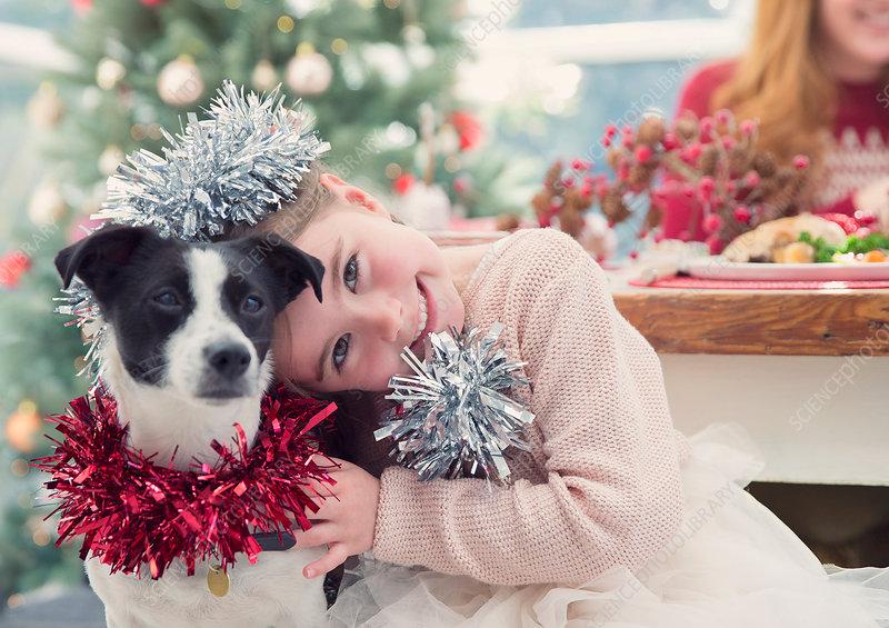 Girl hugging dog at Christmas