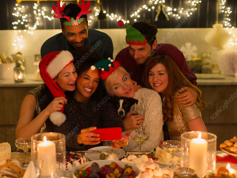 Friends taking selfie at Christmas table