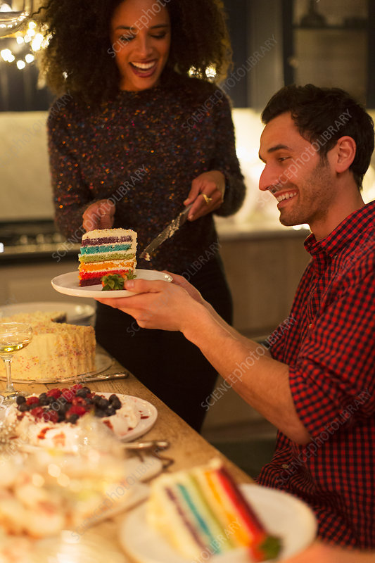 Woman serving layer cake to man at table