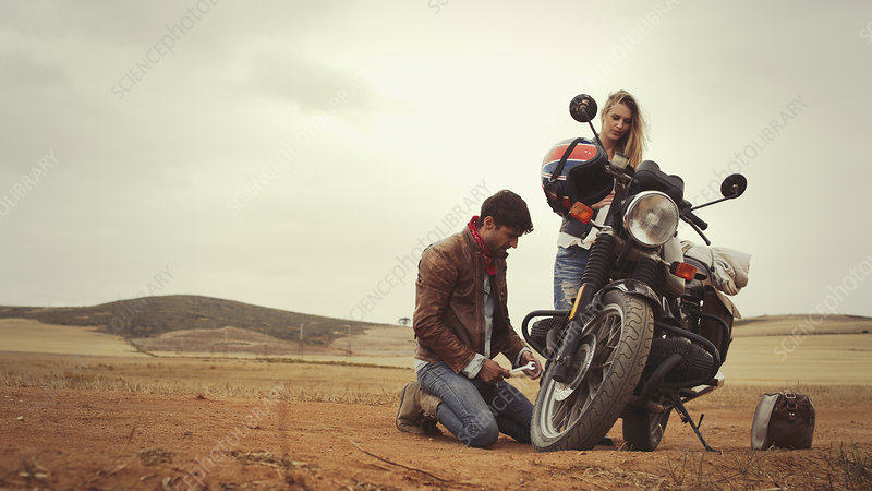 Young couple repairing motorcycle