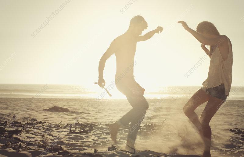 Playful couple dancing on sunny beach