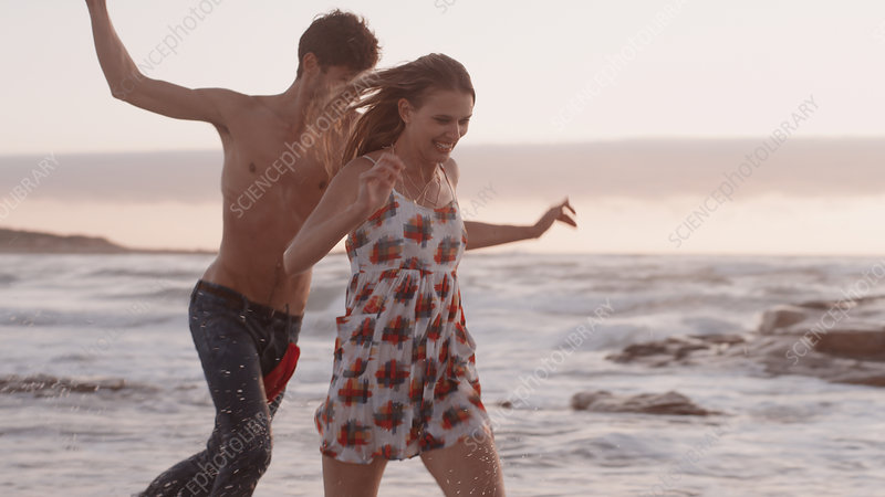 Playful young couple running on beach