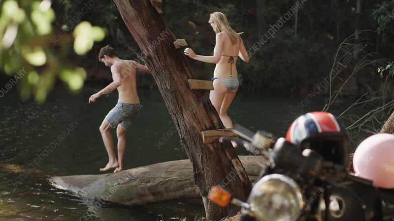Young couple on log at lakeside