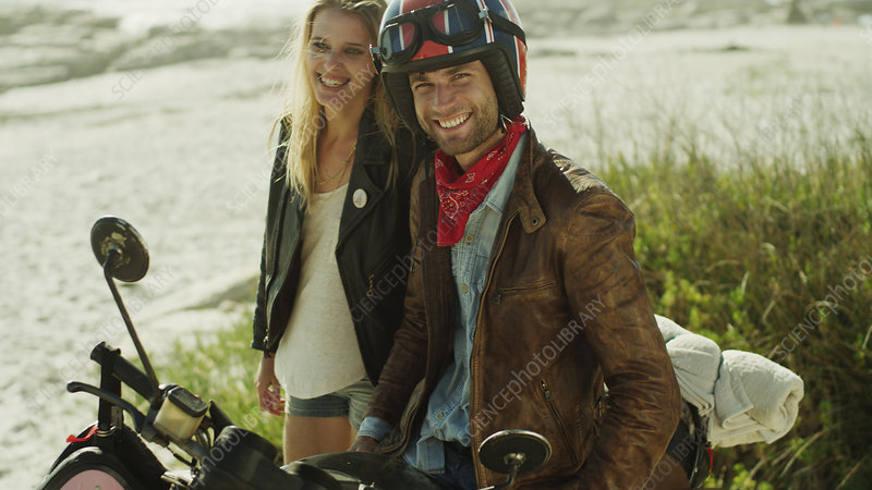 Young couple at motorcycle on beach