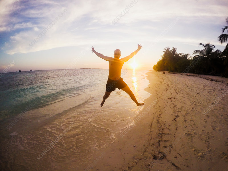 Man jumping on tropical beach at sunset