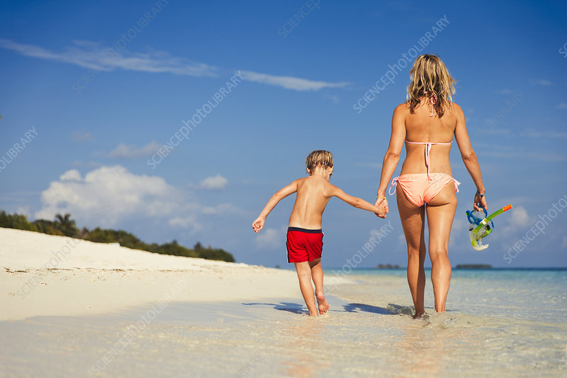 Mother and son walking on tropical beach