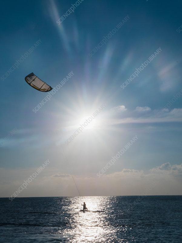 Parasailing on ocean under sunny blue sky