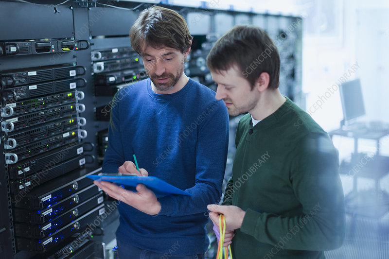 Server room technicians with clipboard