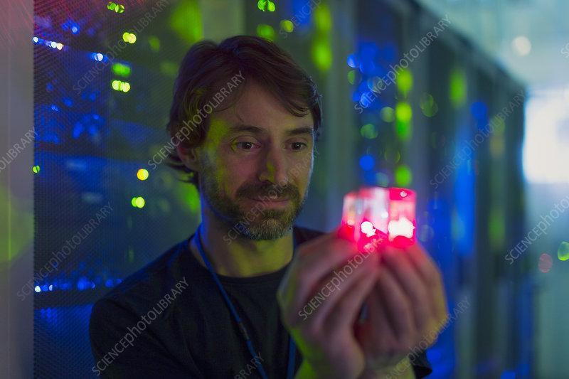 Server room technician holding cube
