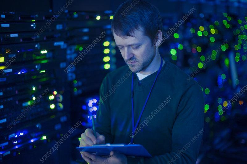 Server room technician taking notes