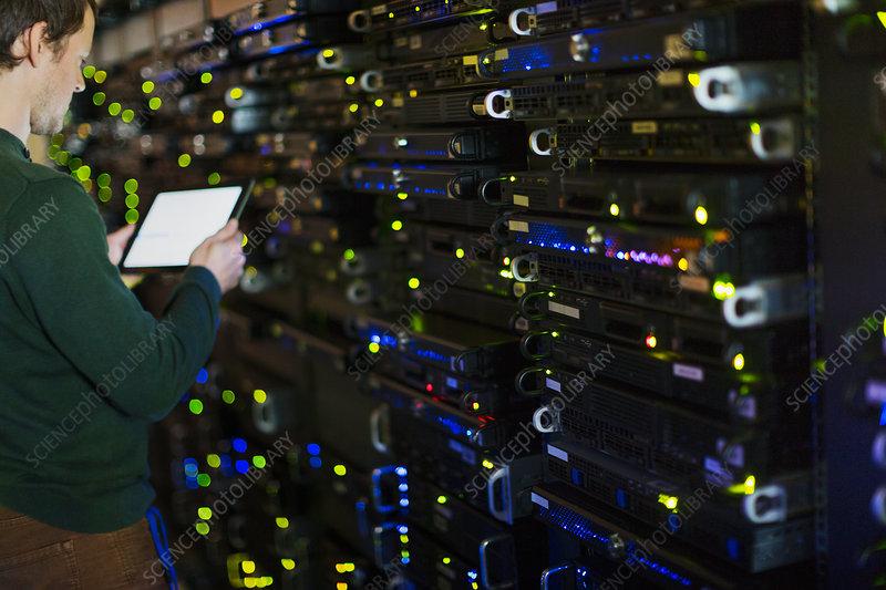 Server room technician using tablet