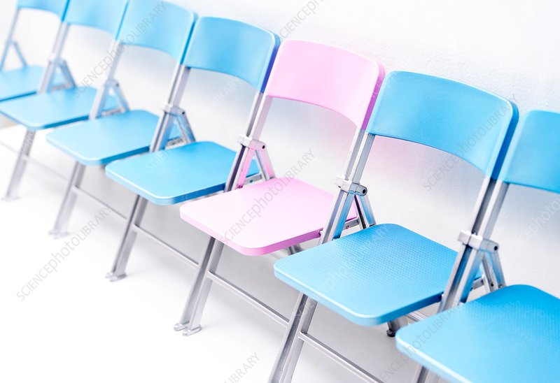 One pink chair in a row of blue chairs