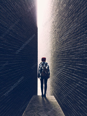 Woman in a narrow brick alleyway