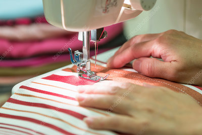 Hands guiding fabric in sewing machine