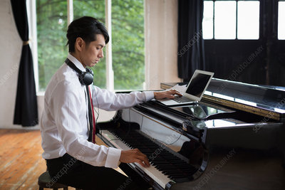 Young man playing piano and using laptop