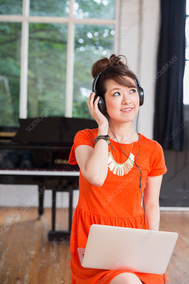 A girl in headphones using laptop