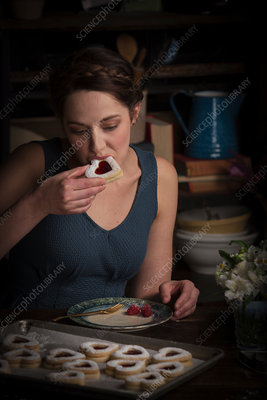 Woman sitting eating a biscuit