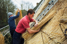 Two men thatching layering straw