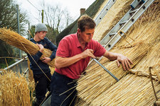 Two men thatching a roof with straw