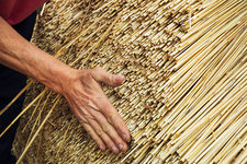 Close up of a man thatching a roof