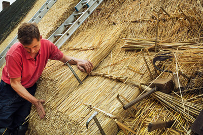 Man using wooden mallet, thatching