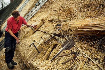 Man thatching a roof, shears, a leggett