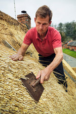 Man dressing a thatch using a leggett