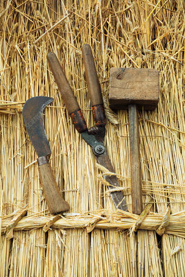 Mallet, shears and a bill hook on straw