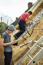 Two thatchers thatching a roof
