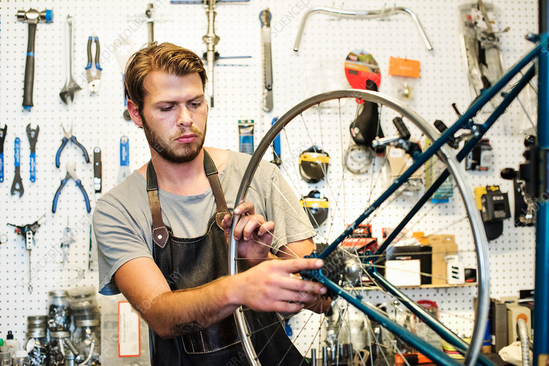 A man working in a bicycle repair shop - Stock Image - F016