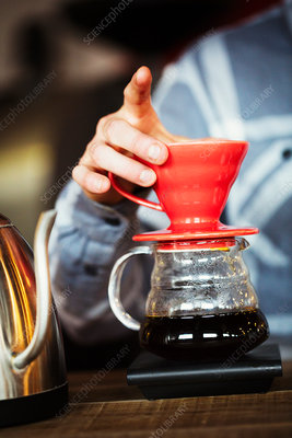 A man brewing coffee and tasting it