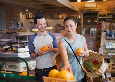 Couple shopping for oranges in market