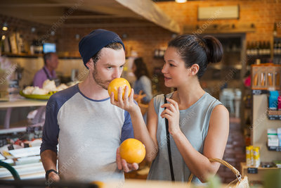 Couple smelling grapefruits in market