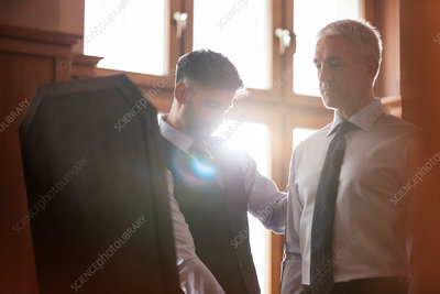 Tailor fitting businessman at mirror