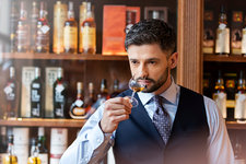 Well-dressed man whiskey tasting