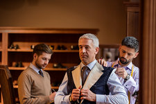Tailors fitting businessman for suit