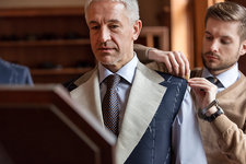 Tailor fitting businessman for suit