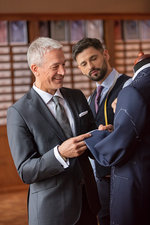 Tailor and businessman examining suit