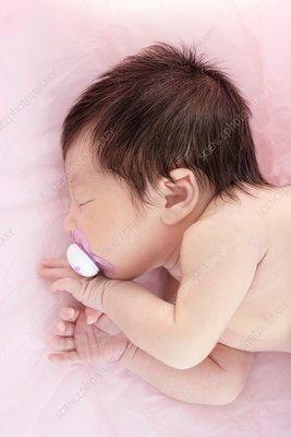 Newborn baby girl with dummy in mouth