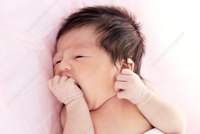 Newborn baby girl with hand in mouth
