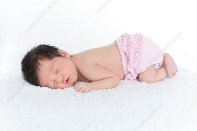 Newborn baby girl in pink nappy, asleep