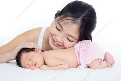 Mother stroking newborn baby girl's head