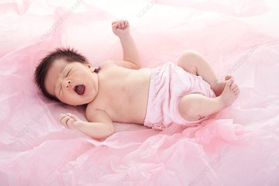 Newborn baby girl in pink nappy, yawning